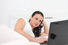 Attractive young woman working on her laptop at home. Photo of the Attractive young woman working on her laptop at home Stock Image