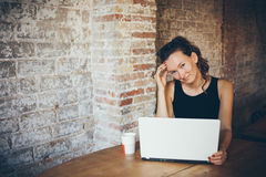 Attractive young woman is working on the laptop while sitting in a loft cafe. Brick wall is on the background. Royalty Free Stock Photo