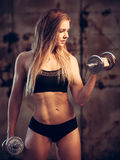 Attractive young woman working out with dumbbells in an abandone Royalty Free Stock Photo