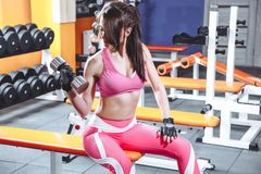Attractive young woman is working out with dumbbells in gym. royalty free stock photos