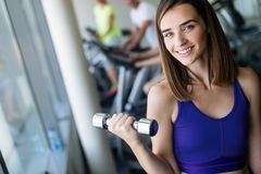 Attractive young woman working out with dumbbells at a gym. royalty free stock photos