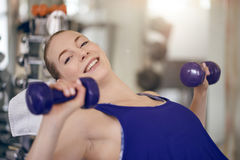 Attractive young woman working out in a gym royalty free stock image