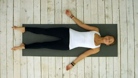 Attractive young woman working out at home, doing yoga exercise, lying in Shavasana Corpse or Dead Body Pose , resting