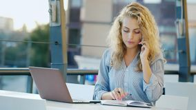 Attractive young woman working on site in summer cafe. It uses laptop stock video footage