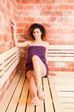 Attractive young woman wrapped in purple towel and smiling Stock Photography