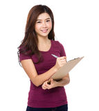 Attractive young woman writes with a clipboard Royalty Free Stock Photography