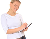 Attractive young woman writing on clipboard Royalty Free Stock Images