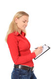 Attractive young woman writing on clipboard Royalty Free Stock Photos