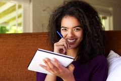 Attractive young woman writing ideas in book Stock Images