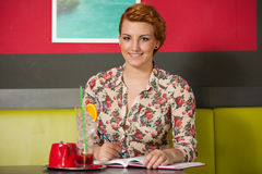 Attractive young woman writting a note in cafe Stock Images