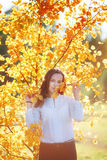 Attractive young woman in yellow autumn leaves, sunlight. Vertical shoot royalty free stock photos
