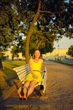 Attractive young woman in yellow dress, sitting in a summer park on a bench Stock Photography