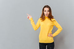 Attractive young woman in yellow sweater pointing finger up Stock Images