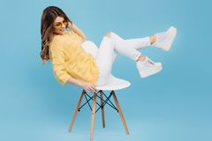 Attractive young woman in yellow sweater posing on blue background. Pretty girl in yellow glasses. Attractive young woman in yellow sweater posing on blue Stock Image