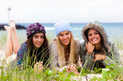 Attractive Young Women at the Beach. Three attractive young women lie on the beach together with the ocean in the background. Horizontal shot Stock Photography
