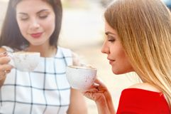 Attractive young women drink coffee in summer city. Lifestyle, friendship and people concept royalty free stock photo