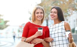 Attractive young women drink take away coffee in summer city royalty free stock images