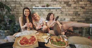 Attractive young women in front of the camera playing very concentrated in a PSP enjoying the time together with pizza stock footage