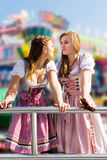 Attractive young women at German funfair Oktoberfest with traditional dirndl dresses. Two attractive young women having fun at German funfair Oktoberfest with Royalty Free Stock Photography