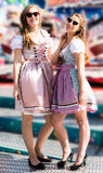 Attractive young women at German funfair Oktoberfest with traditional dirndl dresses. Two attractive young women at German funfair Oktoberfest with traditional Royalty Free Stock Photo