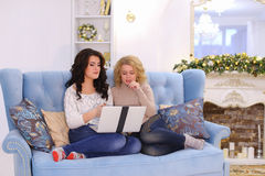 Funny nice friends spend pleasant evening at computer, sitting o royalty free stock photography