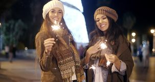 Attractive young women having fun at Christmas. Standing outdoors in stylish winter outfits at night smiling and laughing with sparklers in their hands stock footage