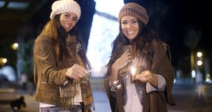 Attractive young women having fun at Christmas. Standing outdoors in stylish winter outfits at night smiling and laughing with sparklers in their hands stock video