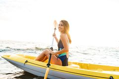 Attractive young woman kayaking stock photography