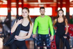 An attractive young woman standing in a fitness center posing with a physical rope over her shoulder. Royalty Free Stock Image