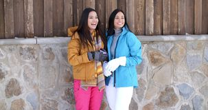 Attractive young women in stylish winter fashion. Two attractive young women in stylish winter fashion standing laughing and chatting against a rock wall of a stock video footage