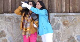 Attractive young women in stylish winter fashion. Two attractive young women in stylish winter fashion standing laughing and chatting against a rock wall of a stock footage