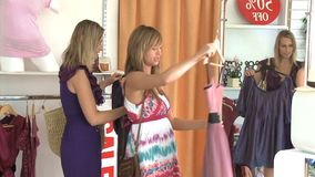 Attractive young women trying dresses looking at the mirror stock footage