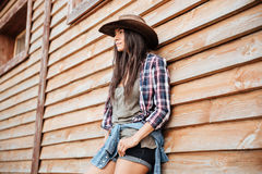 Attractive young womna cowgirl in hat standing near the house Royalty Free Stock Photography