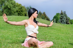 Attractive youngl woman meditates on green lawn. Beautiful woman meditates on green lawn with katana sword  put on feet Stock Photo