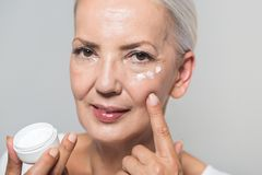 Attractive youthful woman in her fifties. Applying skin cream or moisturiser to her cheek bone from a small jar in a health and beauty concept Royalty Free Stock Images