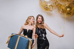 Attractive ypung women in black luxury dresses celebrating birthday party with big present and balloons on white