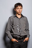 Attractiveness of grey. Young man in steel-blue shirt standing on grey background with hands in pockets Royalty Free Stock Image