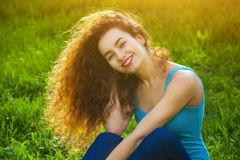 Attraente, ragazza con capelli ricci che si siedono sull'erba verde sul prato inglese e che sorridono al fotografo Fotografie Stock