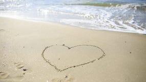 Attraktion för förälskelsehjärtatecken på sandstranden Royaltyfria Foton
