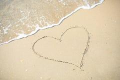 Attraktion för förälskelsehjärtatecken på sandstranden Royaltyfria Bilder