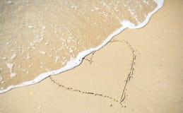 Attraktion för förälskelsehjärtatecken på sandstranden Arkivfoton