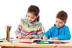 Attraktion för två lilla ungar med färgpennor tillsammans royaltyfri foto