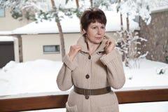 Attraktiv äldre kvinna som poserar på utomhus- terrass i vinter Arkivfoto
