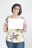 Attraktiv äldre kvinna som rymmer ett tomt vitt ark av papper fo royaltyfri fotografi