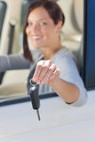 Attraktiv affärskvinna i den nya bilen som visar tangenter Arkivfoto