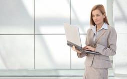 Attraktiv affärskvinna med bärbar dator i händer Arkivbild