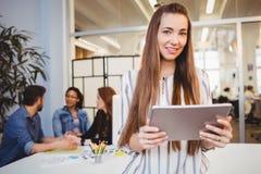 Attraktiv affärskvinna som använder den digitala minnestavlan i mötesrum arkivfoton