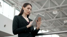 Attraktiv affärskvinna som använder en digital minnestavla, medan stå framme av fönster i förbise för kontorsbyggnad lager videofilmer