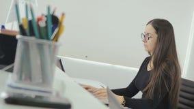 Attraktiv affärskvinna som arbetar med bärbara datorn i kontoret arkivfilmer