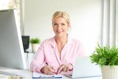 Attraktiv affärskvinna som gör någon skrivbordsarbete royaltyfri bild